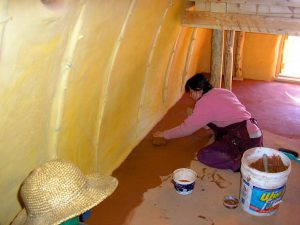 woman finishing a natural earth floor